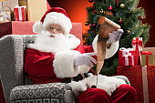 Santa Claus with wishlist in hands