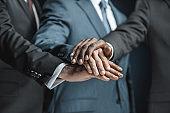 multiethnic businessmen holding hands