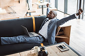 handsome african american businessman with laptop relaxing on sofa in cafe