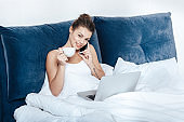 Young woman talking on phone, working on laptop and having morning coffee in bed