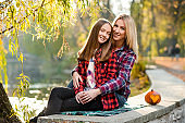 Blonde woman hugging her pretty daughter both smiling