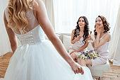 excited bridesmaids looking at bride