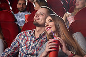 Smiling beautiful couple embracing and watching movie at cinema.