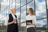 two businesswomen on meeting outdoors near office building