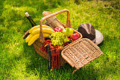 Close-up view of wicker picnic basket with fruits and wine, plaid and hat on green lawn