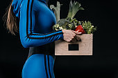 Cropped shot of athletic woman in sportswear holding basket with fresh vegetables, healthy living concept