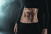 woman's muscular body isolated on black. sport concept