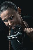 portrait of young fitness woman training with dumbbells isolated on black.