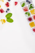top view of ice cubes with berries and fruits isolated on white