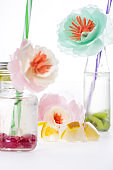 refreshing fruity drinks with decorative flowers and ice cubes isolated on white