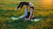 Family couple practicing yoga on the grass at sunset. Healthy lifestyle