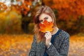 Happy young woman with a beautiful colored yellow leaf enjoying the autumn day