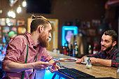 Bartender Talking to Visitor at Pub Counter