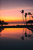 Beautiful Sunrise with silhouette coconut palm tree and swimming pool in beautiful luxury hotel resort