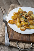 Roasted young potatoes with thyme in white plate