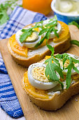 Sandwiches with boiled eggs, yellow tomatoes and arugula