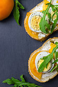 Sandwiches with boiled eggs, yellow tomatoes and arugula.