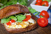 Sandwich with dark bread, eggs, tomatoes and arugula.