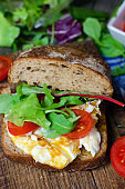 Sandwich with dark bread, eggs and tomatoes.