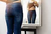woman checking her body in front of mirror