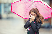 Young girl with flu blowing her nose with a tissue paper under spring rain. Pre-teen girl sneezing and wearing warm clothes against cold weather. Depression, illness allergy under rain