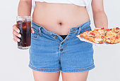 Woman holding glass of cola and pizza with Jeans too tight on belly fat and paunch, Diet concept, Weight lose concept.
