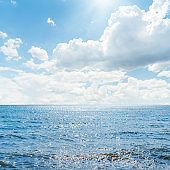 blue sea with sun reflections and blue sky with clouds
