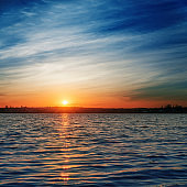 orange sunrise over river in deep blue sky with clouds