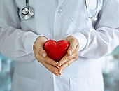 Doctor with stethoscope and red heart shape in hands on hospital background'n