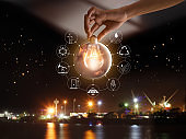 Hand holding light bulb in front of global show the world's consumption with icons energy sources for renewable, sustainable development. Ecology concept. Elements of this image furnished by NASA.