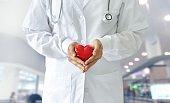 Medicine doctor holding red heart shape in hands on hospital background, medical concept