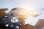 Stethoscope with icon medical on tablet and wooden table background