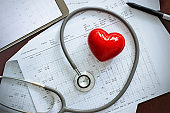 Stethoscope with red heart shape and annual heart health exam report, medical health care concept