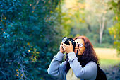 The female photographer is photographing the forest and the birds in a beautiful green forest.