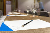 Pencil over the paper on the table of workplace with Glass of waterin the seminar or conference hall room, Business meeting concept