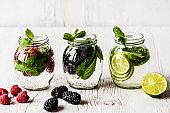 Three kinds of detox water with blackberry, strawberry, lime on white wooden background
