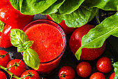 Fresh tomato detox smoothie in a glass on a black slate board. Close-up