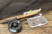 Fly fishing rod ,flie and a landing net on the old wooden table. All ready for fishing.