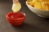 Fingers dips crunchy snack chip into bowl with red sauce.