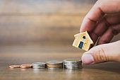 Coin money and house model on wooden background