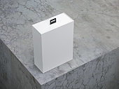 White box packaging with black hang tab on concrete table