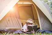 young man tourist lying and reading book in tent at camping site in forest. Outdoor activity in summer. Adventure traveling in national park.