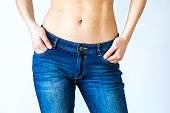 Close up view of woman belly and jeans