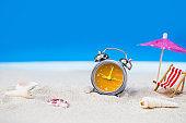 old retro clock on sand beach