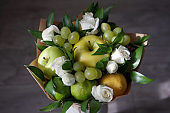 Bouquet of fruits and flowers. Apple, lemon, lime, grapes, white roses and russus.
