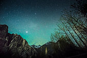 Starry green sky above high mountains on winter night Leh Ladakh India.
