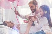 Cheerful loving family surprising their mom