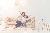 Adorable child and her mom having fun on sofa