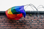 Gay pride flag stuck in barbed wire over a brick wall