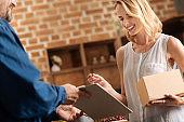 Joyful pretty woman receiving a parcel